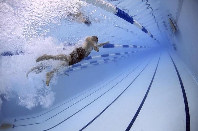 Mensch der Schwimmt um Muskeln aufzubauen